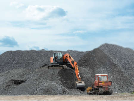 A heavy excavator and a bulldozer are working in a crushed stone factory Фото со стока