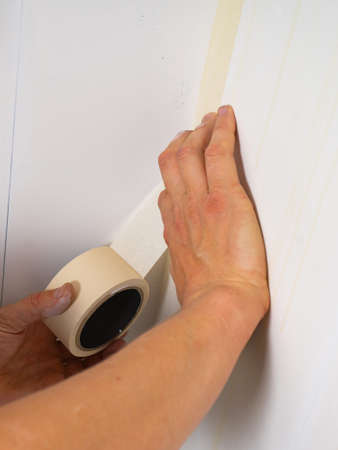 Human hands holding adhesive tape and preparing for painting. Close Up.