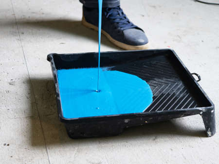A jet of blue paint. The blue paint is poured into cuvette for rollers.