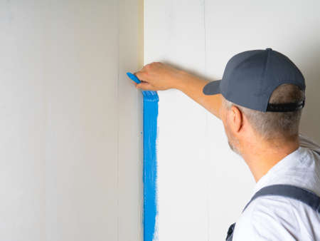 The painter applies blue paint with a brush on the wall. Фото со стока