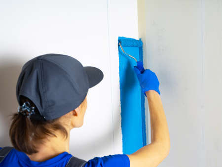 Female painter painting a white wall with a roller in blue color renovations or construction concept..