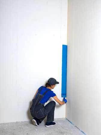 Female painter painting a white wall with a roller in blue color renovations or construction concept.