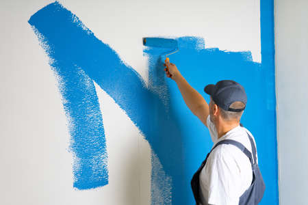 Male painter painting a white wall with a roller in blue color renovations or construction concept.