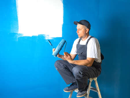 The painter sits on a ladder and thinks about the right choice of tools for work. concept of tool selection. Фото со стока