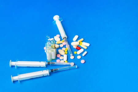Close up medications, tablets, ampoules and syringe on blue background. Concept of treatment of influenza and viruses.