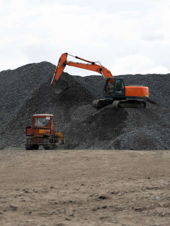 A heavy excavator and a bulldozer are working in a crushed stone factory.