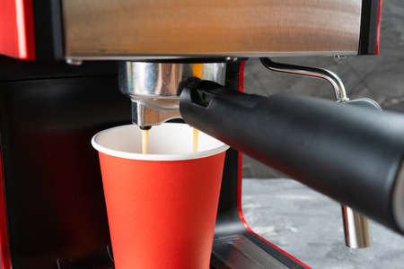 Red coffee machine fills a red paper cup. Coffee to go. Close-up