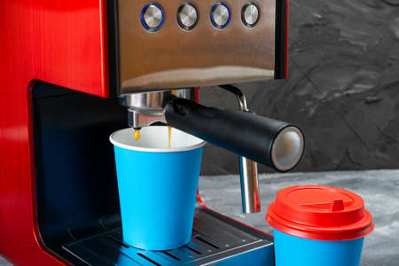 Red coffee machine fills a blue paper cup. Coffee to go.