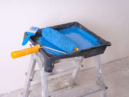 Cuvette for rollers with a roller and brush filled with blue paint stands on a stepladder.