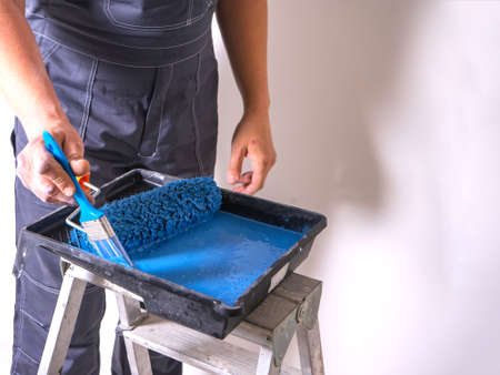 The painter dips his brush in paint bath of blue paint. Cuvette for rollers on a stepladder.