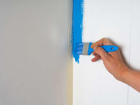 A professional painter uses a brush to apply paint to the wall. Painting the walls in blue.