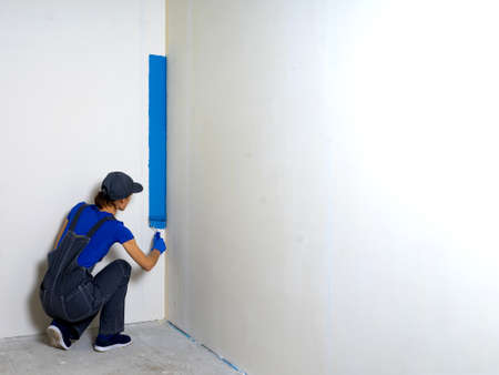 Female painter painting a white wall with a roller in blue color renovations or construction concept