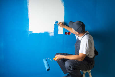 A lazy painter paints a wall sitting on a ladder