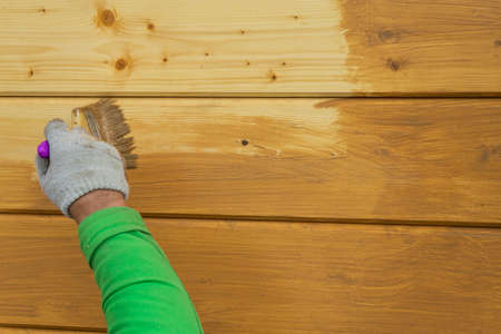 A worker's hand in a glove, painting a wooden house. Covering a wooden house with a protective compound.