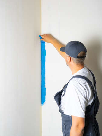 The painter applies blue paint with a brush on the wall