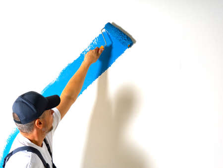 Male painter painting a white wall with a roller in blue color renovations or construction concept