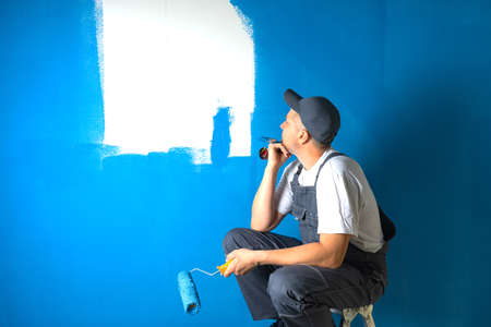 The painter sits on a ladder and thinks about the right choice of tools for work 版權商用圖片