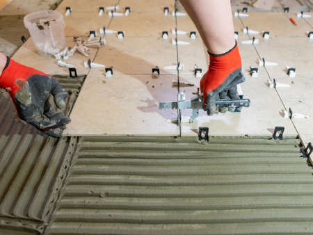 A worker is leveling the ceramic tile with wedges and clips. Tile leveling system