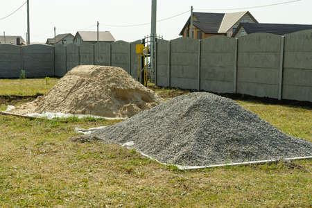 Piles of rubble and sand are stacked on the construction site.