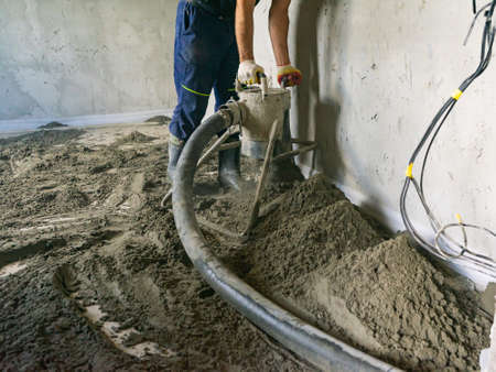 Worker at a construction site screed floor. Leveling semi-dry floor screed. 版權商用圖片