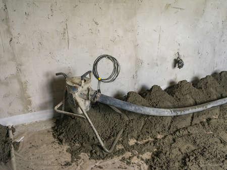 Machine application of semi-dry floor screed is processed in residential building. Machine running screed flooring.