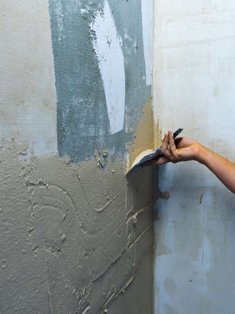 House improvement by worker. Hand with a spatula. Worker trowels putty on wall with finishing putty.