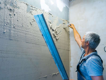 Applying plaster putty to the wall using a aluminum paver screed.