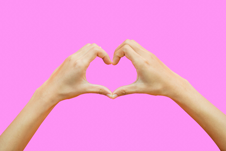 Female hands shaping a heart symbol isolated on pink background include clipping path