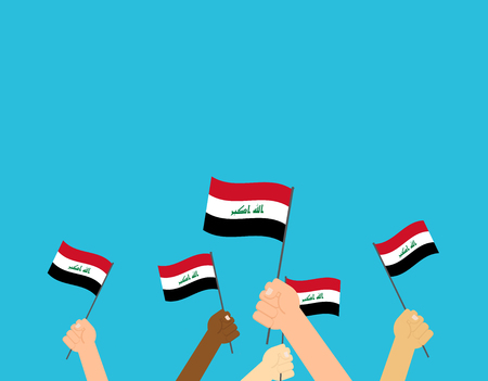Hands holding Iraq flags isolated on blue background
