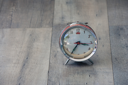 Time Management Concept : Close up red vintage alarm clock be distorted and damaged setting on wooden floor in vintage style.