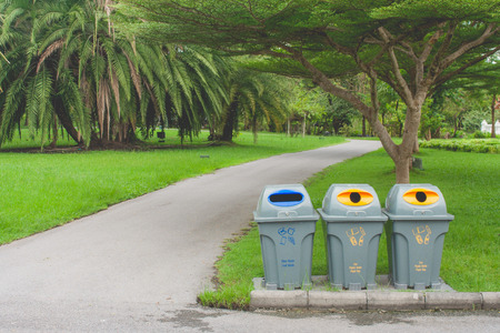 Public recycle bins or segregated waste bins sitting on concrete floor beside walkway in public park with green natural background.
