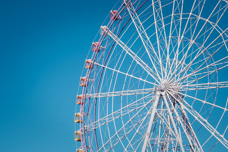 Close up part of colorful ferris wheel with blue sky background at public park in vintage style.