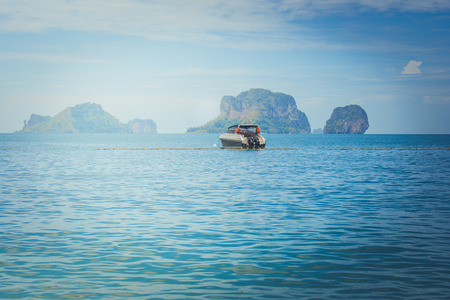 Beautiful seascape view of lonely speed boat floating on the sea with island and blue sky in the background at Railay Beach, Krabi Province, Thailand. 版權商用圖片