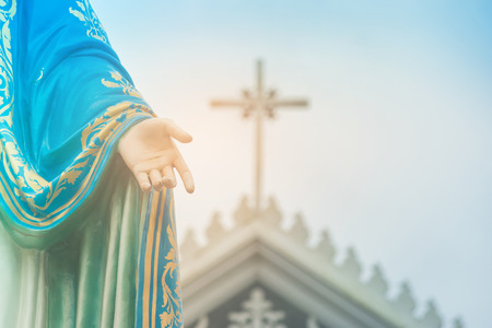 Hand of The Blessed Virgin Mary statue standing in front of the Roman Catholic Diocese with crucifix or cross and blue sky in the background at Chanthaburi Province, Thailand.
