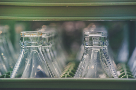 Close up row of used soft drink glass bottles in green container in vintage style. (Selective focus)