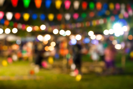 Abstract blurred image of people with bokeh from light in colorful day festival at outdoor garden in evening.