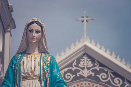 The Blessed Virgin Mary statue standing in front of The Cathedral of the Immaculate Conception at The Roman Catholic Diocese with crucifix and blue sky background at Chanthaburi Province, Thailand.
