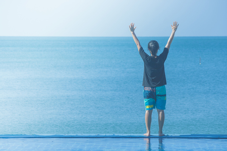 Woman standing on edge of swimming pool with raised hands over head, she looking at seascape view.