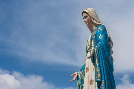 The Blessed Virgin Mary statue standing in front of The Cathedral of the Immaculate Conception at The Roman Catholic Diocese with blue sky background at Chanthaburi Province, Thailand.