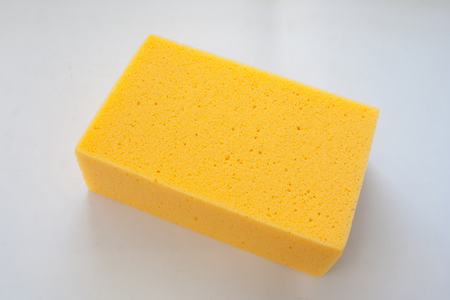 Close up new yellow sponge isolated on white background. (Selective focus)