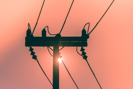 Silhouette of electricity pole and high voltage power line with sunset in the background. (Selective focus)