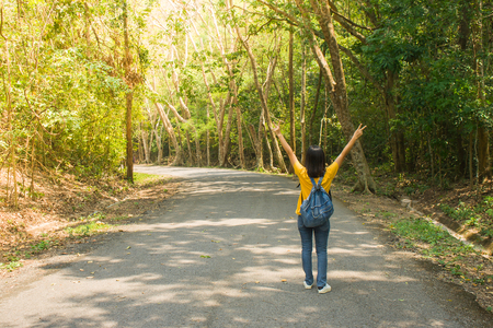 Alone woman traveler or backpacker walking along countryside road among green trees, she raise hands over head and feeling happiness.