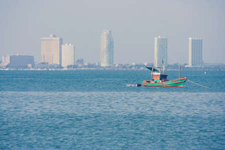 Fishing boat floating on blue sea with skyscraper view in the background. (Selective focus) Stock Photo