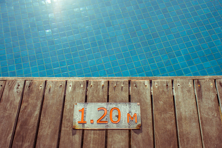 Swimming pool depth signs or markers located on wooden floor beside blue water pool.