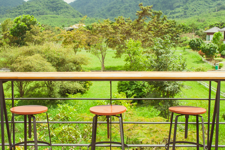 Rows of wooden stools and counter bar on outdoor terrace with beautiful landscape viewpoint at countryside. Imagens