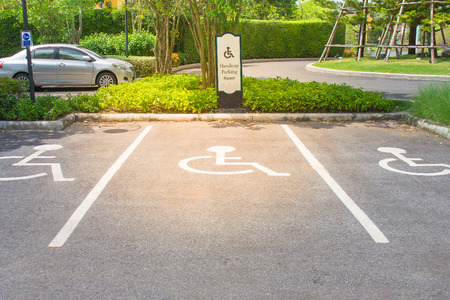 Empty handicap parking areas in parking lot reserved for disabled people at outdoor. (Selective focus)