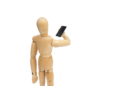 Wooden figure mannequin holding black smartphone isolated on white background. Stockfoto