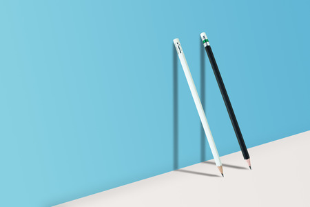 Business Creative and Idea Concept : Black and White pencils standing on white floor and shadow on blue wall.