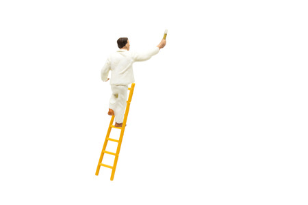 Miniature figurine character as painter standing on wooden ladder and painting wall with paint tools isolated on white background. Imagens