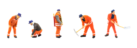 Miniature figurine character as construction worker standing and working in posture isolated on white background.